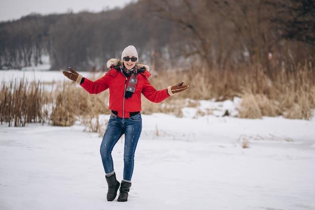 Mujer feliz en chaqueta roja afuera en invierno