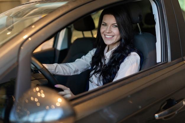 Mujer feliz del cliente que compra un coche nuevo en el centro de reventa.
