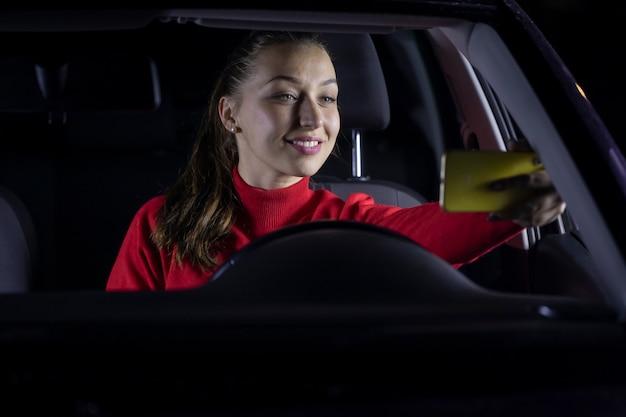 Mujer feliz en el coche por la noche se detuvo estacionado y hablando con la familia por videollamada