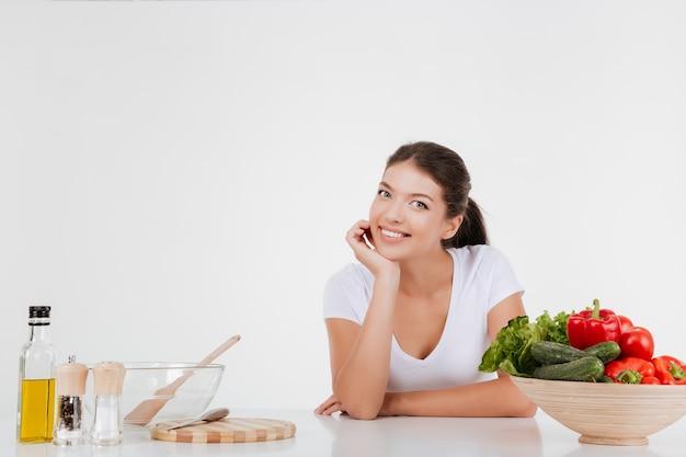 Mujer feliz cocinando con verduras