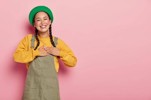 Mujer feliz con coletas tiene expresión apreciada, mantiene las palmas en el corazón, expresa gratitud, agradece la ayuda y los consejos.