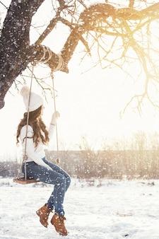 Mujer feliz y columpio de cuerda en paisaje de invierno