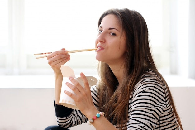 Mujer feliz comiendo fideos
