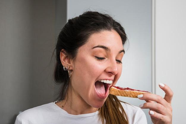 Mujer feliz comiendo mermelada y pan