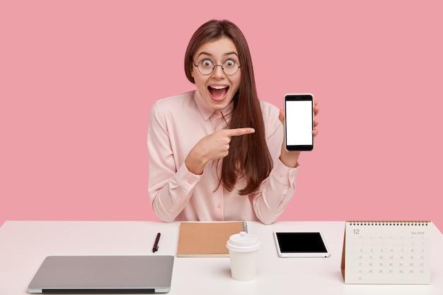 La mujer feliz y complacida apunta al teléfono móvil con una pantalla simulada, tiene una expresión facial asombrada, es perfeccionista, se esfuerza por lograr la perfección