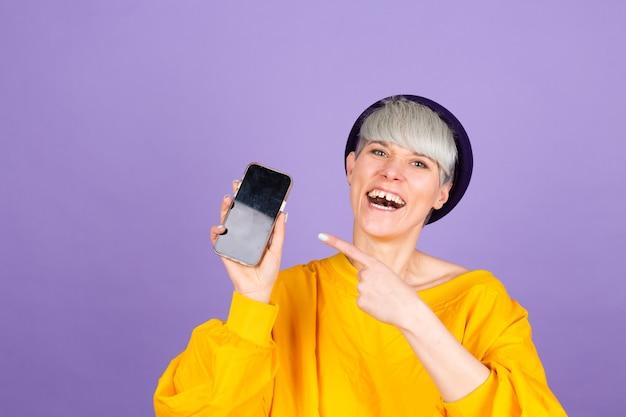 Mujer feliz complacida señala con el dedo índice en la pantalla en blanco, mostrando un dispositivo moderno