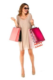 Mujer feliz del comprador con los bolsos de compras del colorfull en fondo aislado