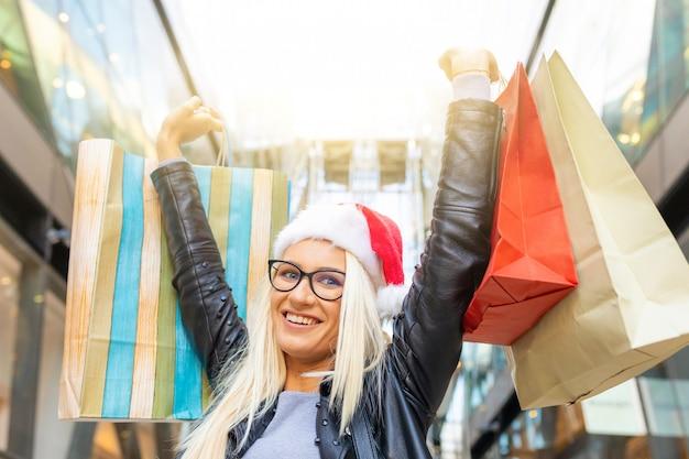 Mujer feliz con las compras del sombrero de santa en tiempo de la navidad