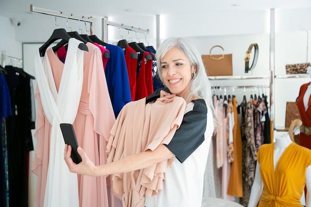 Mujer feliz de compras en la tienda de ropa y consultar a un amigo en el teléfono celular, mostrando el vestido elegido. tiro medio. concepto de comunicación o cliente boutique