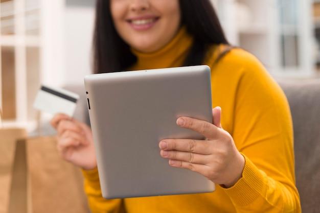 Mujer feliz comprobando la tableta para una nueva compra