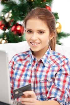 Mujer feliz con computadora portátil y tarjeta de crédito sobre el árbol de navidad.