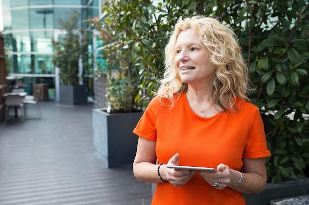 Mujer feliz contenta caminando con tableta