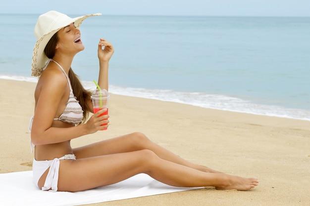 Mujer feliz con una copa de cóctel en la playa