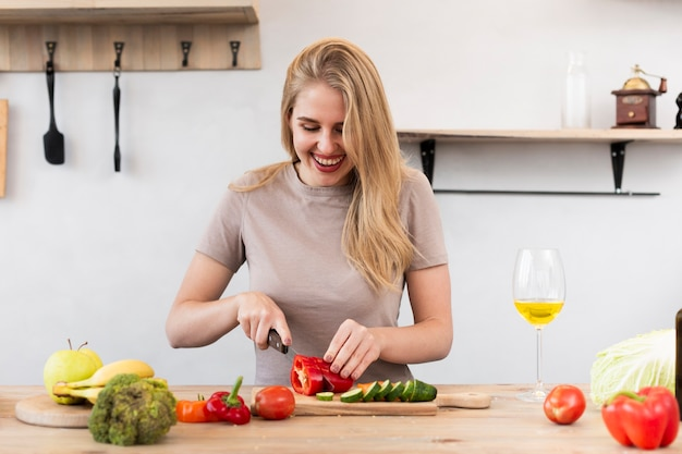 Mujer feliz cortar verduras