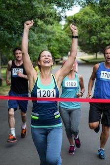 Mujer feliz cruzando la línea de meta