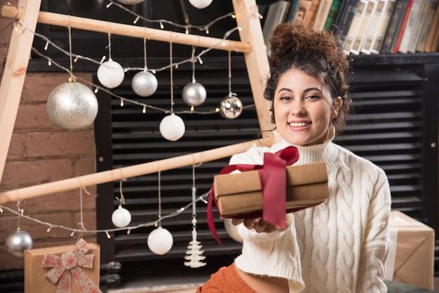 Una mujer feliz dando una caja de regalo con lazo.