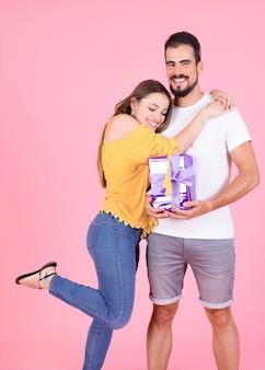 Mujer feliz dando un abrazo a su novio con regalos envueltos sobre fondo rosa