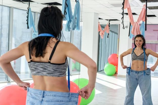 Mujer feliz delgada en jeans de gran tamaño en el gimnasio. estilo de vida femenino. forma y dieta