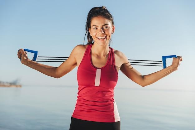 Mujer feliz deportes haciendo ejercicio con expansor de mano