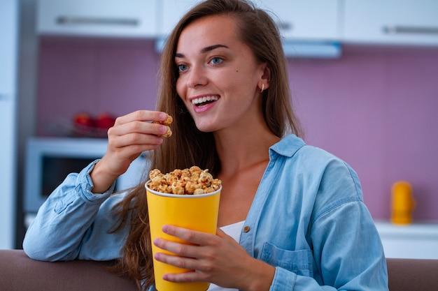 Mujer feliz descansando, riendo y comiendo crujientes palomitas de caramelo durante ver películas de comedia en casa. película de palomitas de maíz