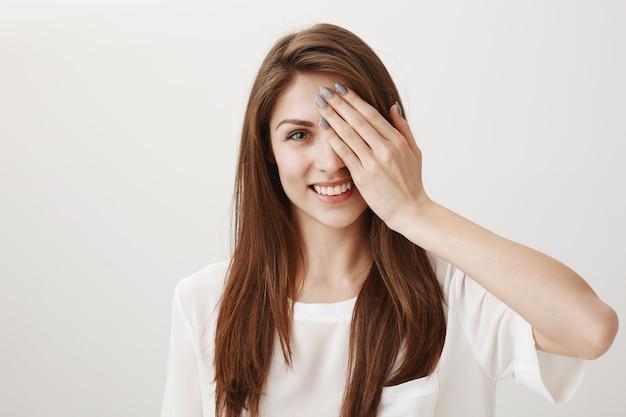 Mujer feliz despreocupada cubre la mitad de la cara y sonriendo complacido
