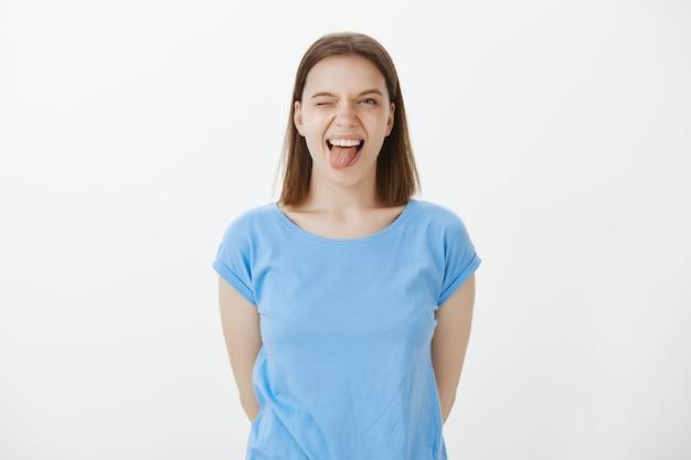 Mujer feliz despreocupada mostrando la lengua y guiñando un ojo alegre