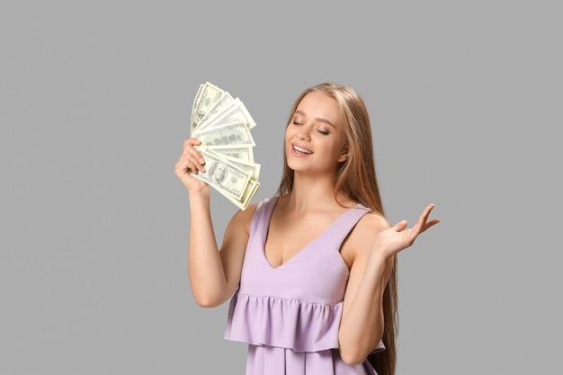 Mujer feliz con dinero sobre fondo gris