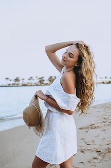 Mujer feliz disfrutando de playa relajante alegre en verano por agua azul tropical