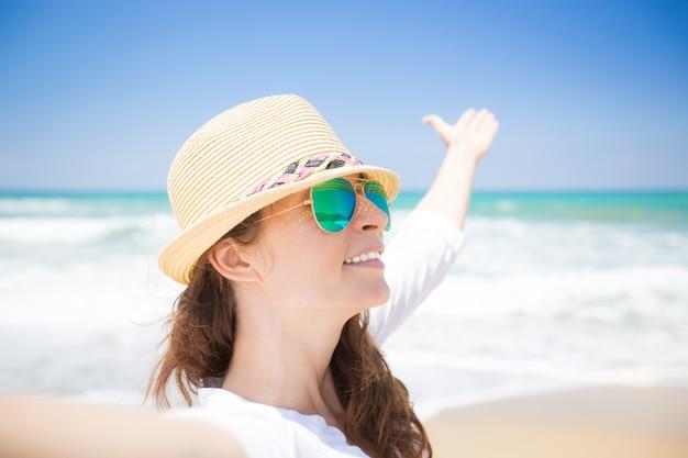 Mujer feliz disfrutando de la vida en la playa.