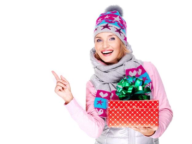 Mujer feliz y divertida con un regalo en una ropa de abrigo de invierno apuntando con el dedo aislado en blanco