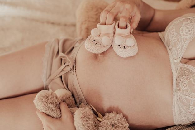 Mujer feliz embarazada con zapatos de bebé en sus manos