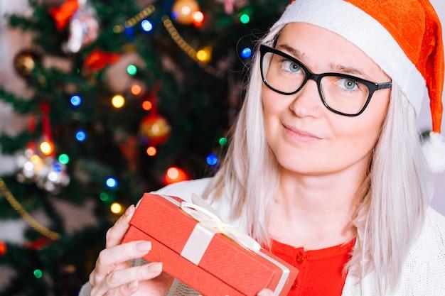 Mujer feliz emocionada de abrir presente en caja de regalo de navidad antes del árbol de navidad