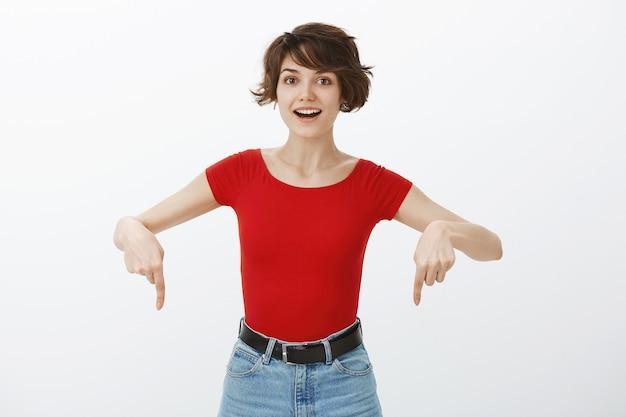 Mujer feliz emocionada mirando asombrado y señalando con el dedo hacia abajo