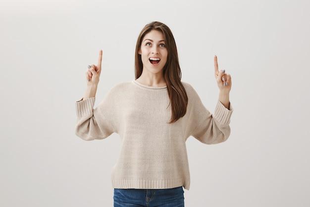 Mujer feliz emocionada mirando y señalando con el dedo hacia arriba y una buena oferta promocional