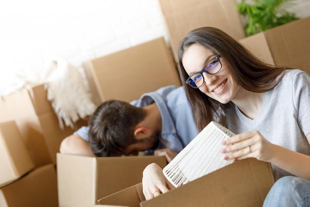 Mujer feliz empacando cosas para mudarse