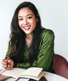 Mujer feliz escribiendo un diario en su oficina
