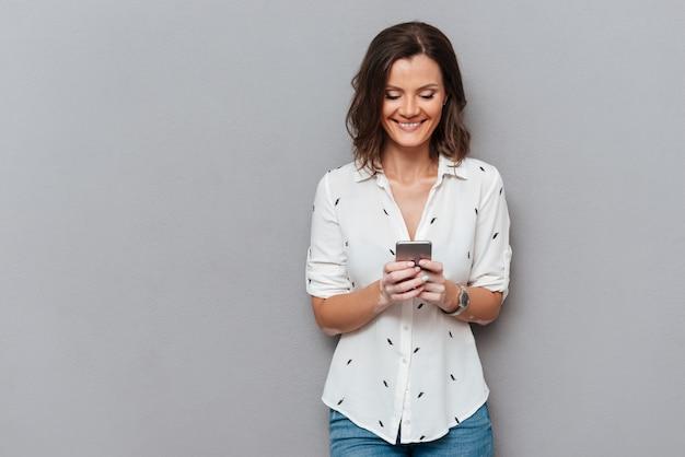 Mujer feliz escribiendo mensajes en su teléfono inteligente en gris