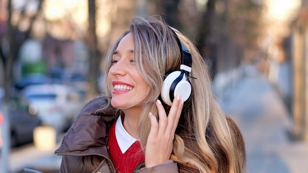 Mujer feliz escuchando música con auriculares inalámbricos