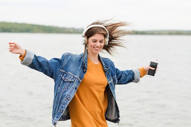 Mujer feliz escuchando música en la naturaleza