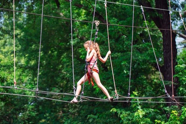 Mujer feliz de la escuela disfrutando de la actividad en un parque de aventura de escalada en un día de verano