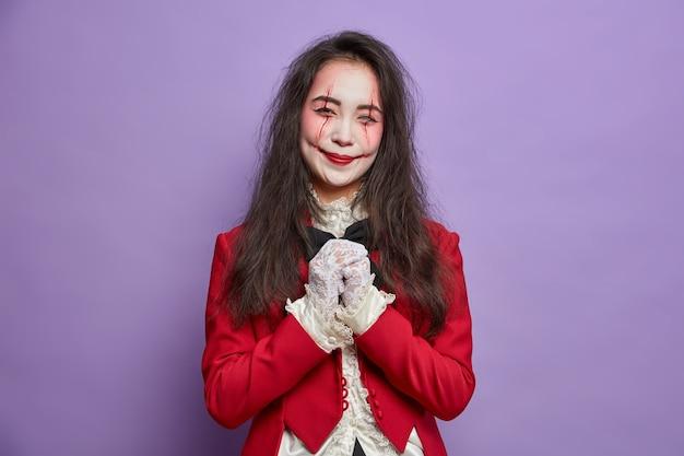 Mujer feliz espeluznante tiene imagen de zombie mantiene las manos juntas usa posturas de maquillaje fantasma para cartel de halloween aislado en la pared púrpura
