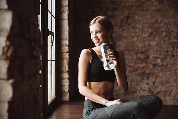 Mujer feliz fitness agua potable y mirar a un lado.