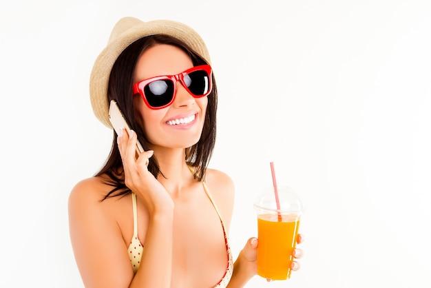 Mujer feliz en gafas y sombrero de verano bebiendo jugo y hablando por teléfono