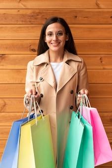 Mujer feliz con gafas sosteniendo bolsas de la compra.