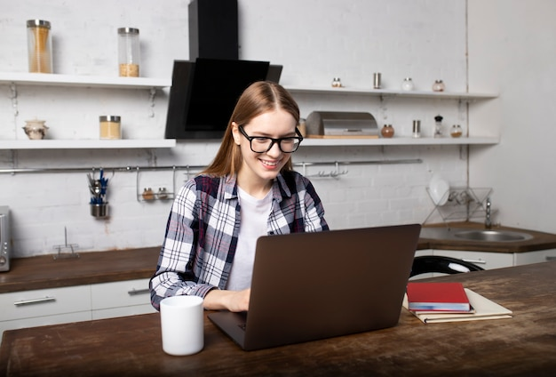 Mujer feliz con gafas trabajando en casa por la mañana. chica tomando café. ella esta usando su laptop