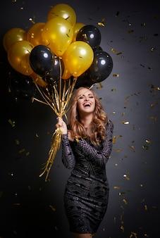Mujer feliz con globos celebrando su cumpleaños