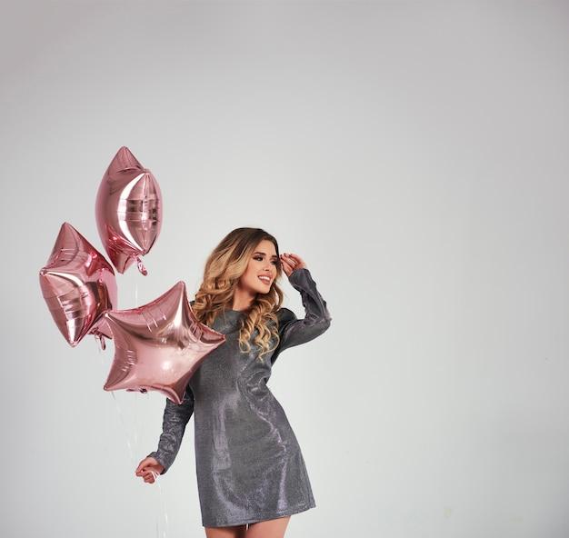 Mujer feliz con globos en forma de estrella mirando espacio de copia