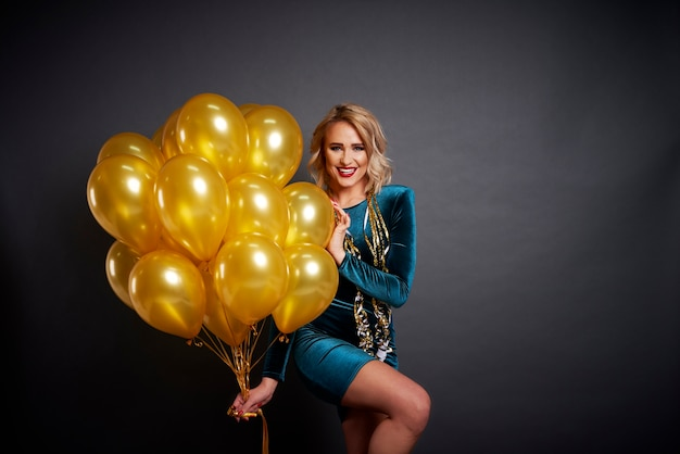 Mujer feliz con globos en tiro de estudio