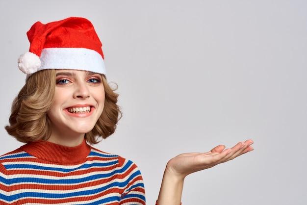 Mujer feliz con un gorro de navidad y un suéter de rayas gestos con sus manos para el año nuevo