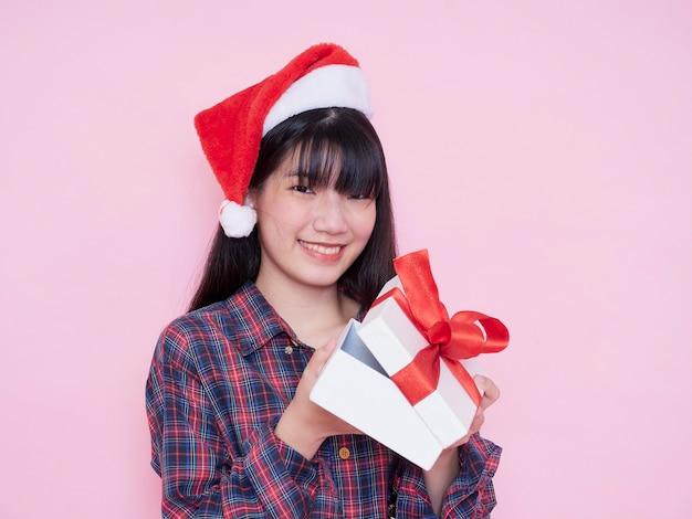 Mujer feliz con gorro de papá noel abriendo caja de regalo de navidad en pared rosa